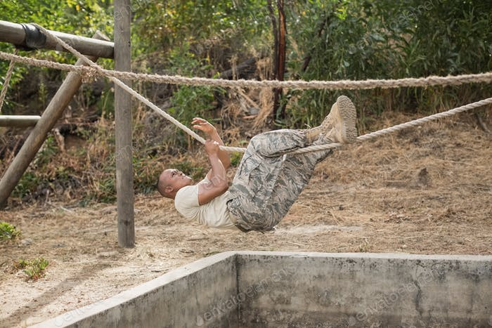 Military soldier climbing rope during obstacle course training