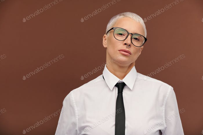 Young stylish masculine woman in formalwear and eyeglasses standing in isolation