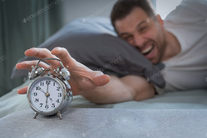 Angry Man Turning Off Alarm-Clock Waking Up Lying In Bed
