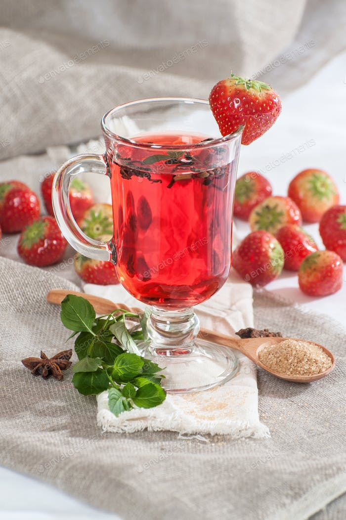 A cup of freshly brewed strawberry tea with fresh mint.
