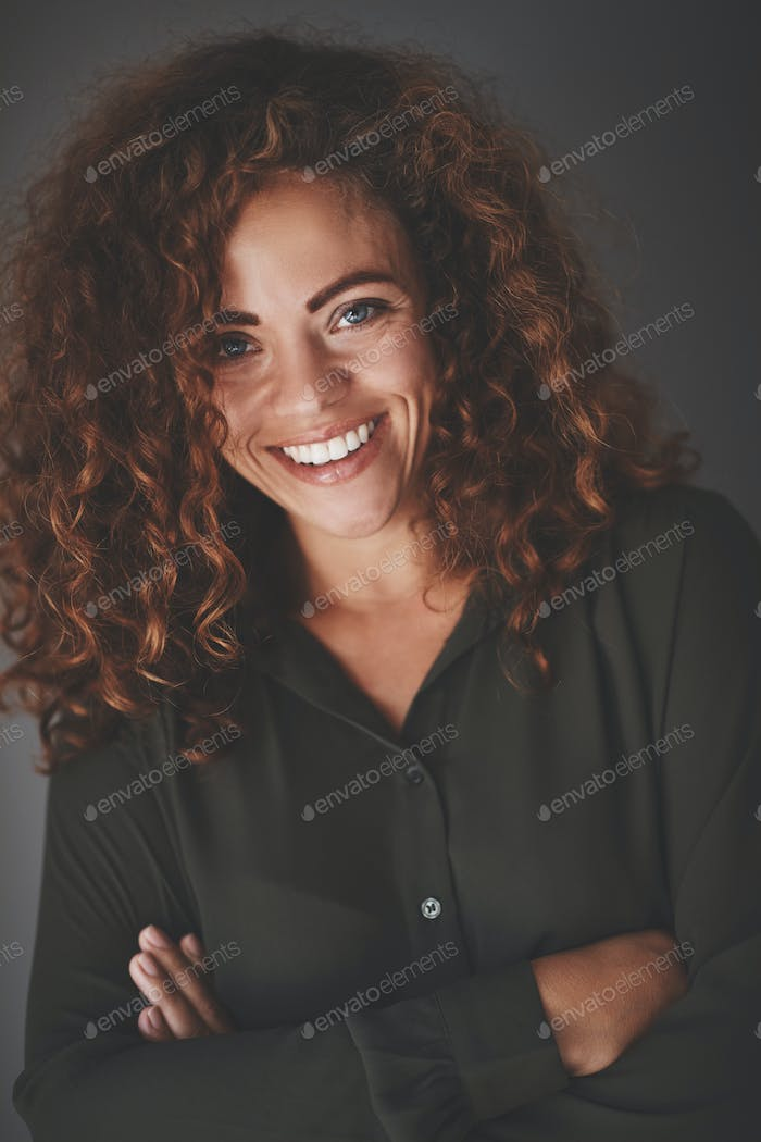 Young businesswoman smiling confidently while standing against a gray background
