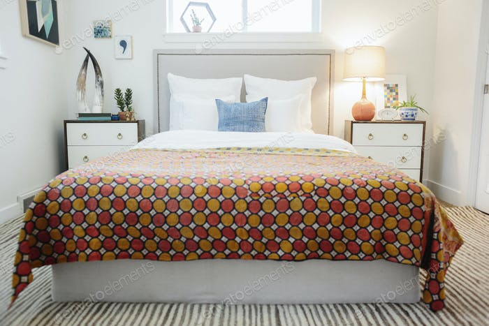 A bedroom in an apartment with a double bed and beside cabinets, and a vivid retro style patterned