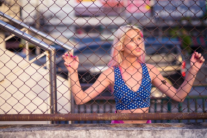 Young beautiful blonde woman against chain link fence outdoors