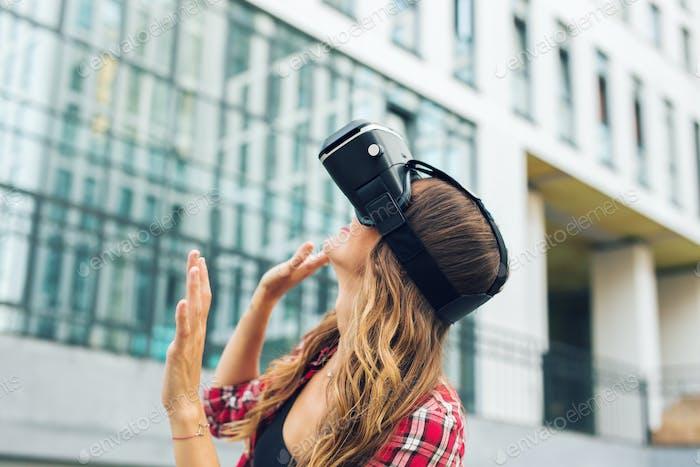 schönes junges Mädchen mit Virtual Reality VR Headset auf der Straße