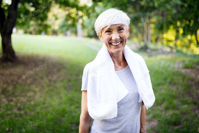 Portrait of smiling sporty senior woman with towel outdoor