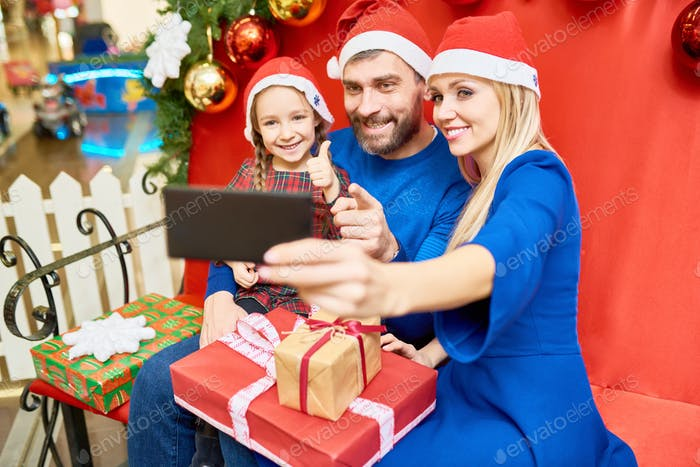 Family taking selfie with Christmas gifts