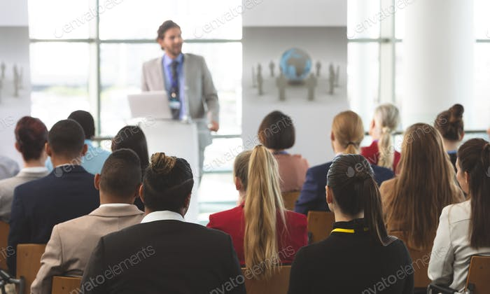 Group of diverse business people listening businessman speak at seminar in modern office