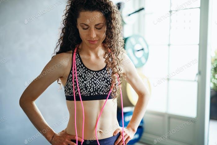 Fit Frau stehend mit einem Springseil im Fitnessstudio