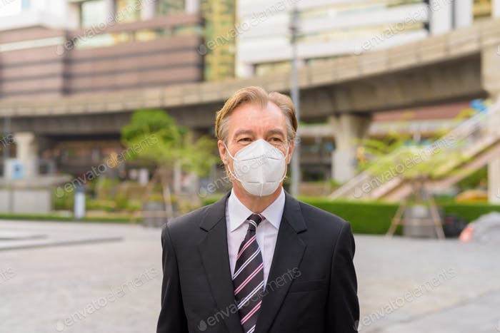 Mature businessman thinking with mask for protection from corona virus outbreak in the city outdoors