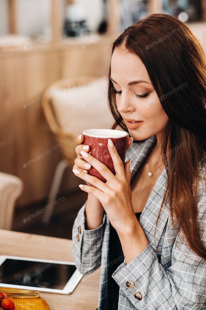ein Mädchen trinkt Kaffee in einem Café, schöne Haare eines Mädchens