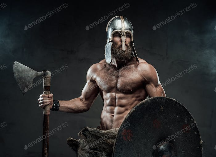 Nordic warrior with axe and shield in studio with spotlight