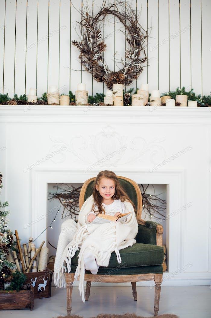 Porträt von 7 Jahren Kind lesen Buch zu Hause auf Weihnachten