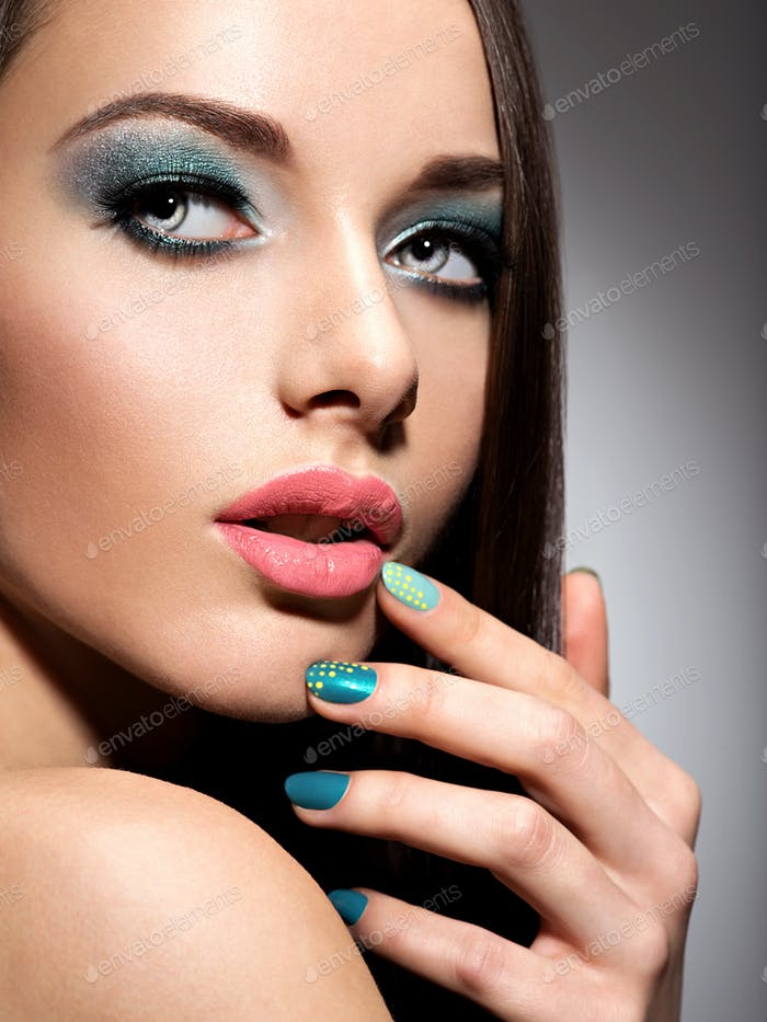 Beautiul fashion young adult girl with turquoise make-up and nai