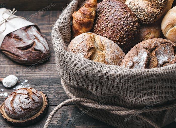 Köstliches frisches Brot in einem Sack auf Holzhintergrund