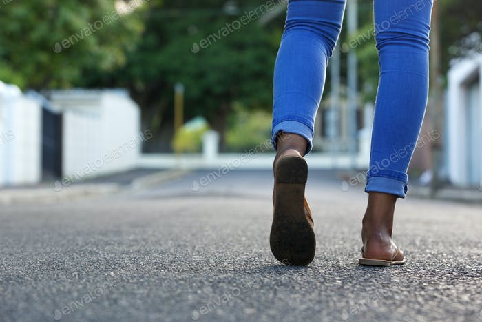 Female legs walking on the road