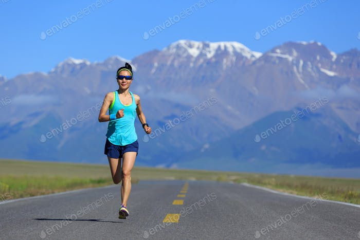 Determined woman runner running on mountain trail