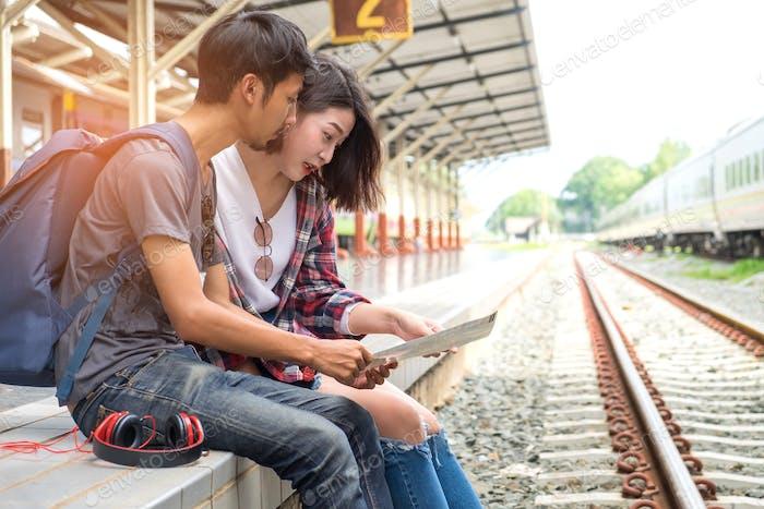 Asiatische männliche und weibliche Touristen planen eine Zugfahrt.