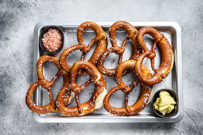 Salted pretzels with sea salt on a kitchen baking pan. White background. Top view