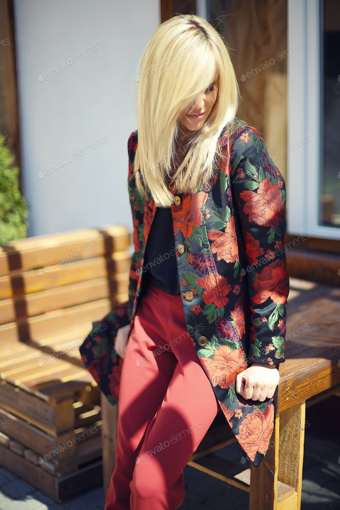young beautiful stylish woman posing on street in floral printed