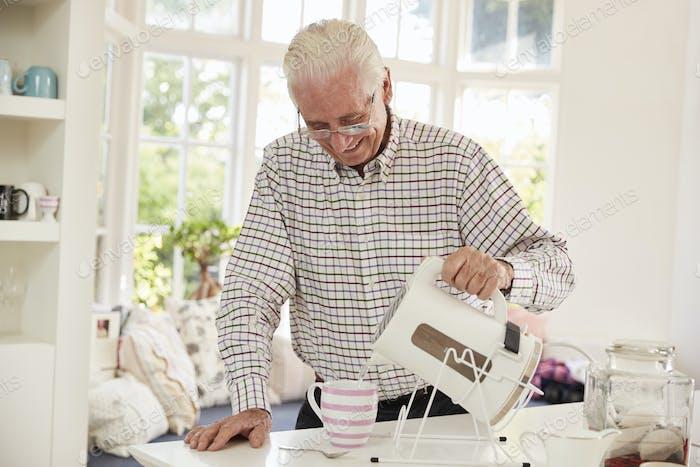 Senior Mann macht Tasse Tee zu Hause