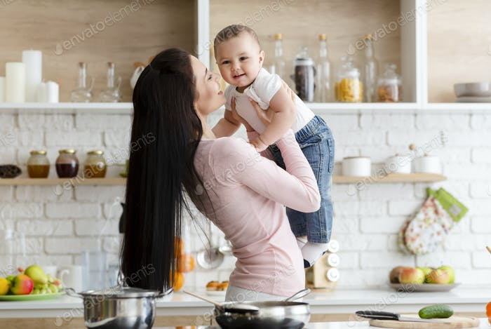 Mother playing with adorable baby son in kitchen