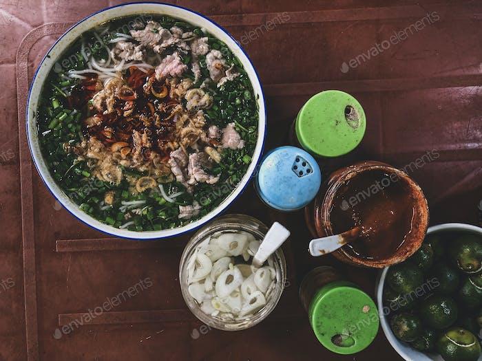 Draufsicht auf einem traditionellen Pho Bo auf einem dunklen Tisch. Pho bo ist Vietnam