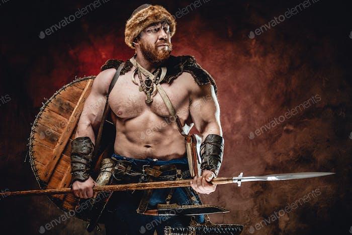 Nordischer Krieger mit Speer und Schild auf dem Rücken in dunklem Hintergrund