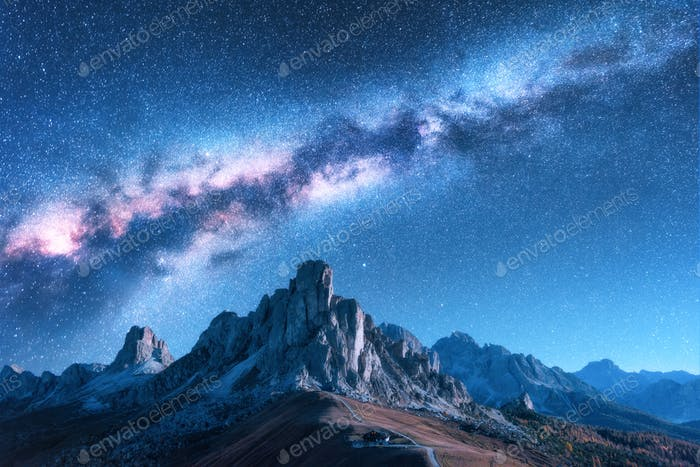 Milky Way above mountains at night in autumn in Dolomites, Italy
