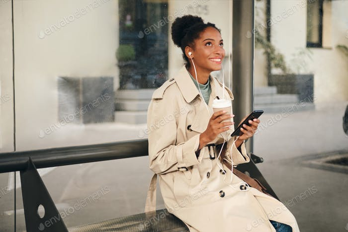 Beautiful African American girl in stylish trench coat happily listening music at bus stop