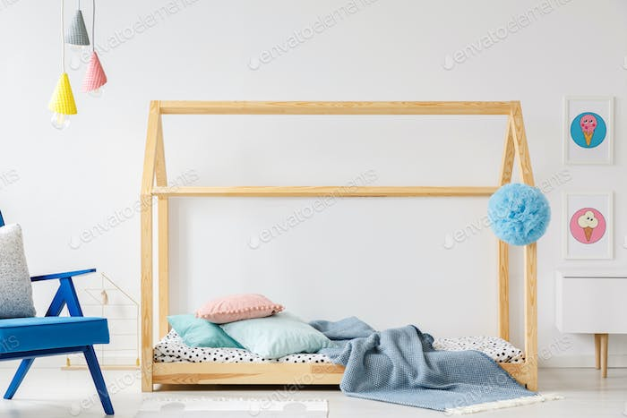 Wooden DIY bed in modern child's bedroom interior with blue armc