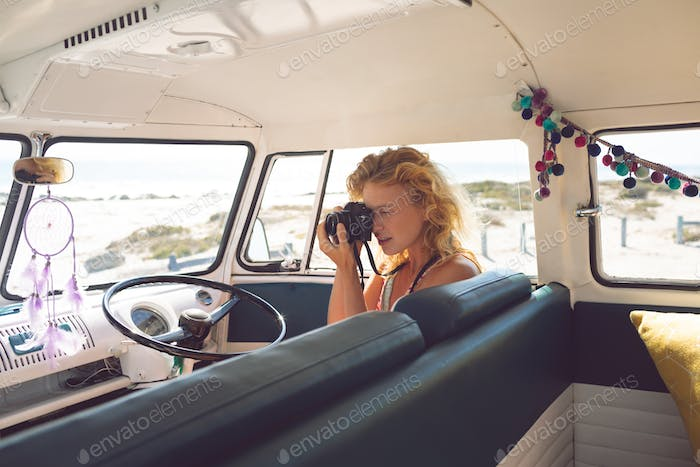 Side view of beautiful Caucasian woman taking photo with digital camera in camper van at beach