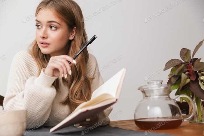 Bild des Denkens kaukasische Frau, die Notizen macht und Tee trinken
