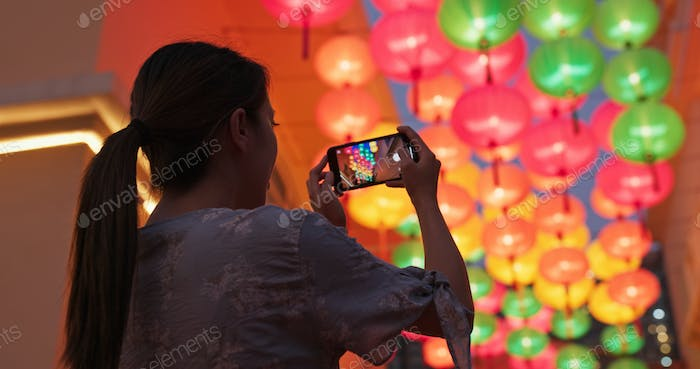 Woman take photo with cellphone on the chinese lantern