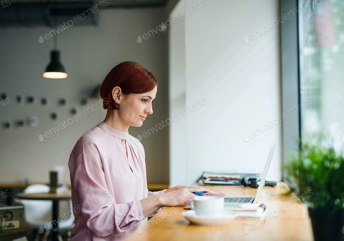 A portrait of woman with coffee sitting at the table in a cafe, using laptop