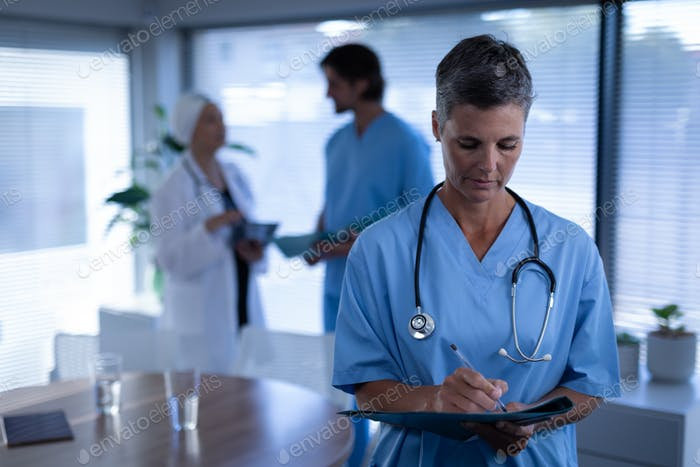 Female surgeon writing in medical report in clinic at hospital