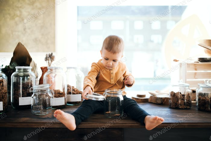 A barefoot small toddler boy sitting on a table in zero waste shop.