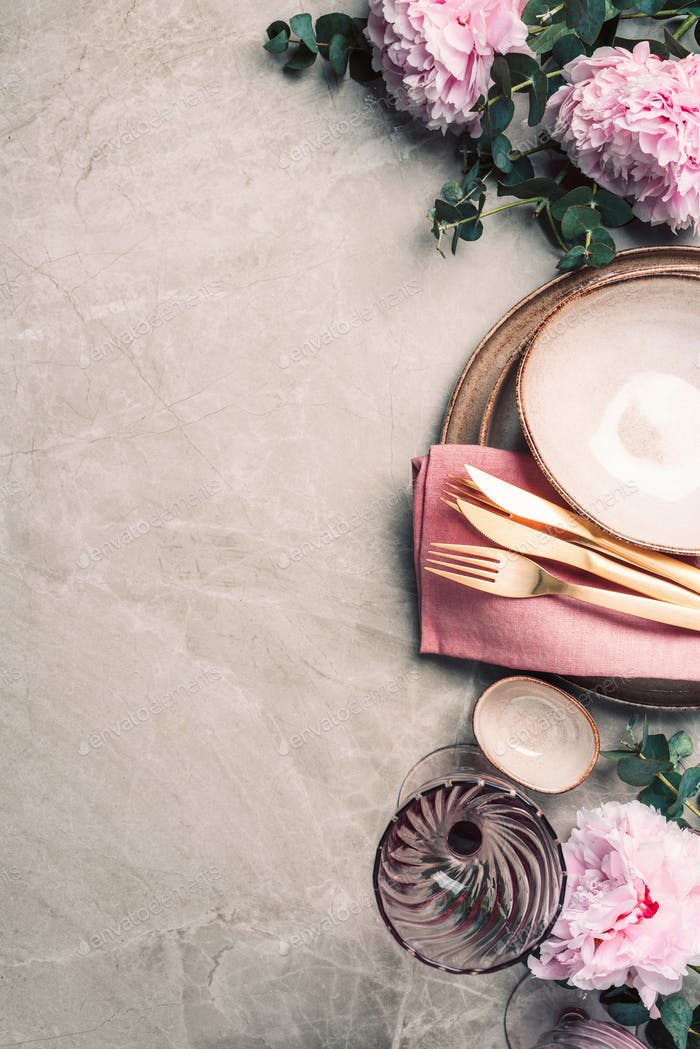 Flat lay composition with peony, eucalyptus flowers, empty plates, napkin, golden cutlery