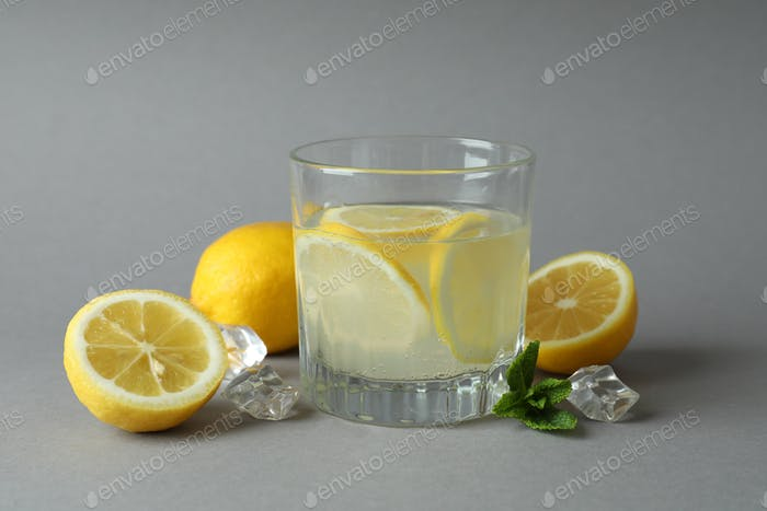 Glass of lemonade and ingredients on light gray background