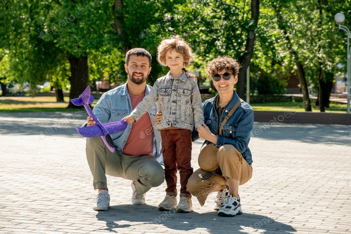 Happy cute little boy and his affectionate young parents spending time in park