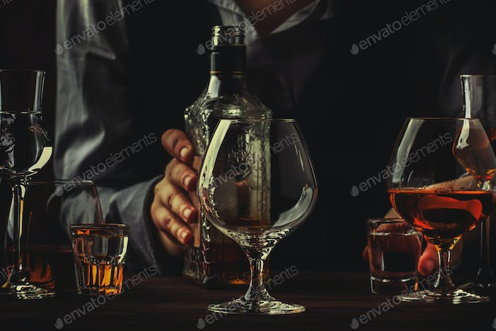 The bartender holding bottle of strong drink in hand and big wine glass