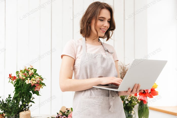 Beautiful sales woman standing near bouquets in flower workshop,