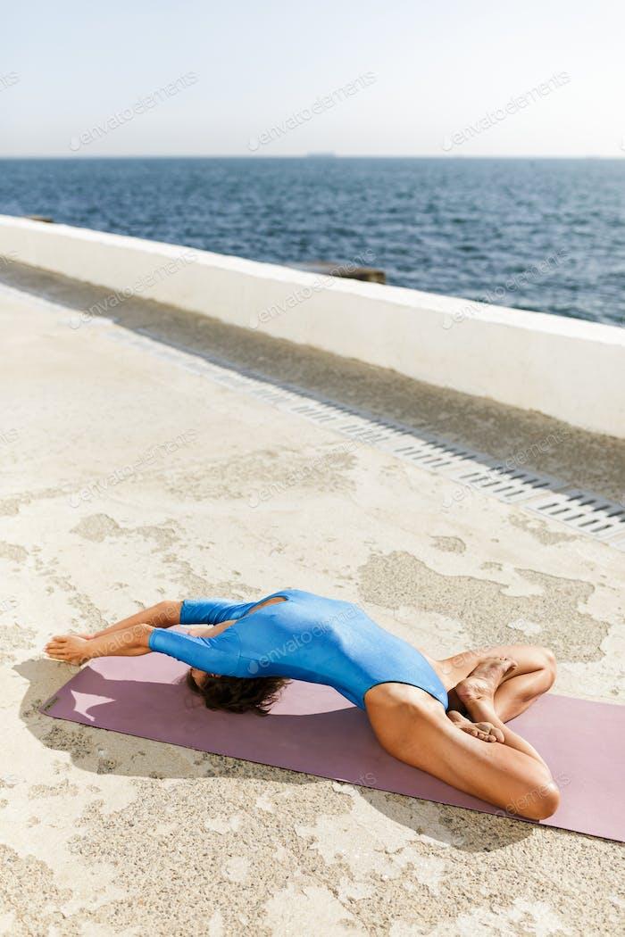 Porträt von schönen Dame im blauen Badeanzug meditieren und praktizieren Yoga am Meer