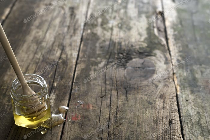 Honey Organic in jar with a wooden stick on an old wooden background , pure natural sweet goodness