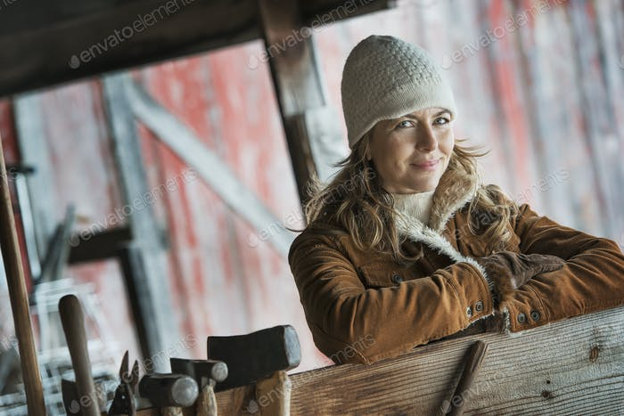 Farming in winter,a woman in a sheepskin coat and row of hand tools hanging on a post.