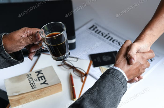 Businessmen holding coffee cup are shake hands.