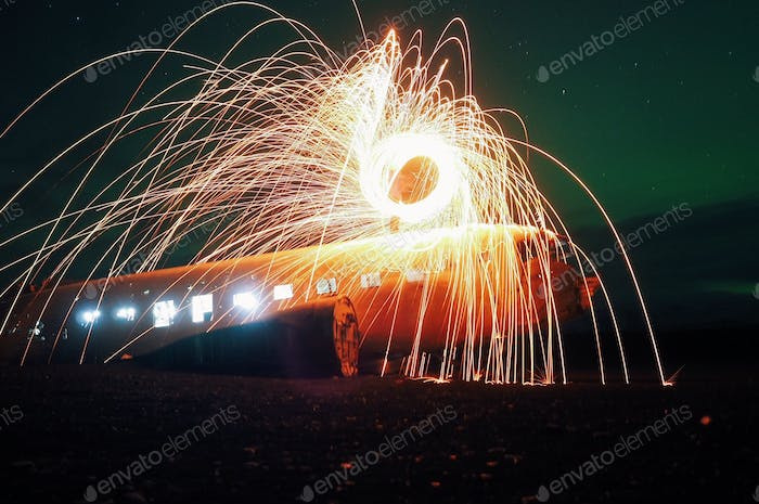 Abandoned DC bomber with steelwool and lights under some northern lights