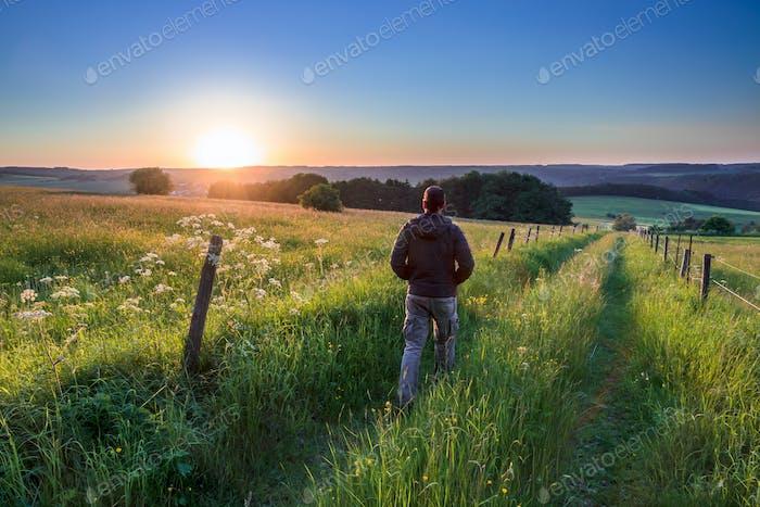 Man walking along Track Towards Sunset