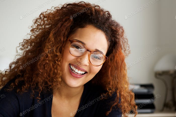 Close up happy young woman with curly hair and glasses