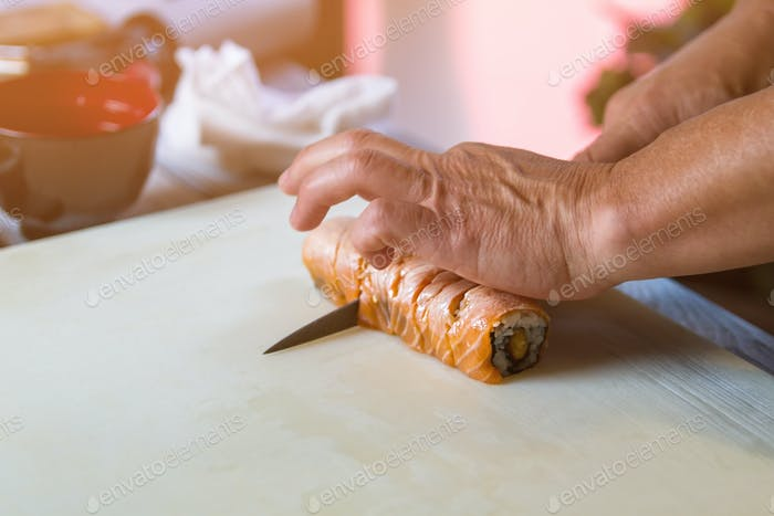 Hands with knife cut sushi.