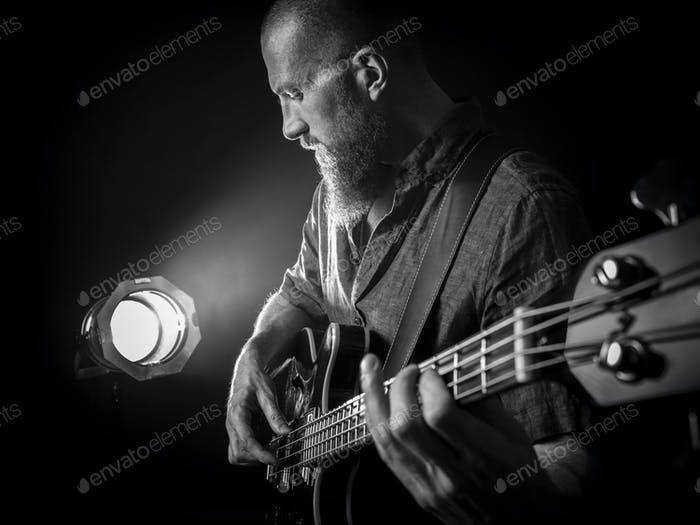 Bearded man playing bass guitar on stage